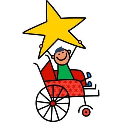 A young boy sits in a wheelchair. He is smiling and holding a star over his head.