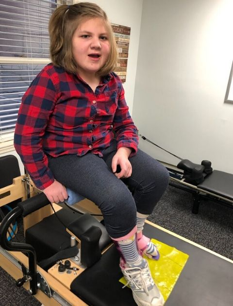 Child with adaptive equipment on a Pilates Reformer.