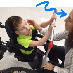 Lisa working with a severely disabled young boy in his wheelchair at yer Aspire Therapy Services physical therapy clinic in Cincinnati, OH located within May We Help on Wooster Pike.