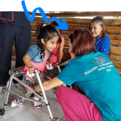 Lisa working with a young girl in a walker with a severe handicap.