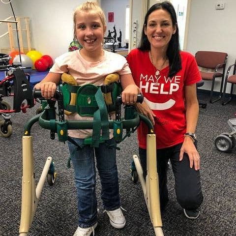 Physical therapist Lisa Davison with a young female patient using a mobility aid. Lisa is wearing a May We Help shirt.