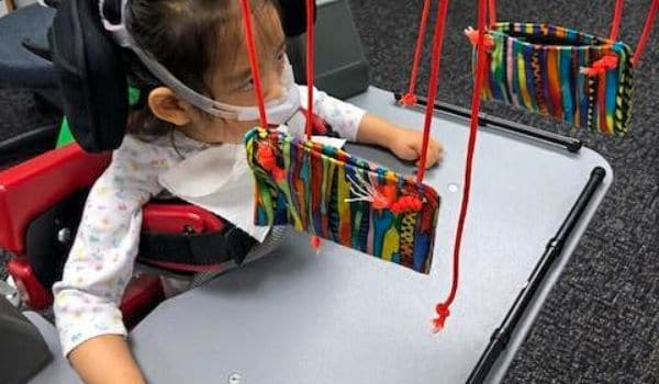 Child using a custom tool during a pediatric physical therapy session.