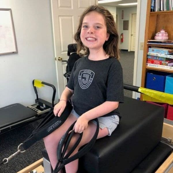 Pilates Reformer with a child using it during a physical therapy session.