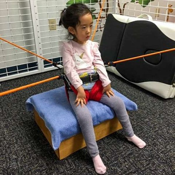 Child using a Universal Exercise Unit during a physical therapy session.